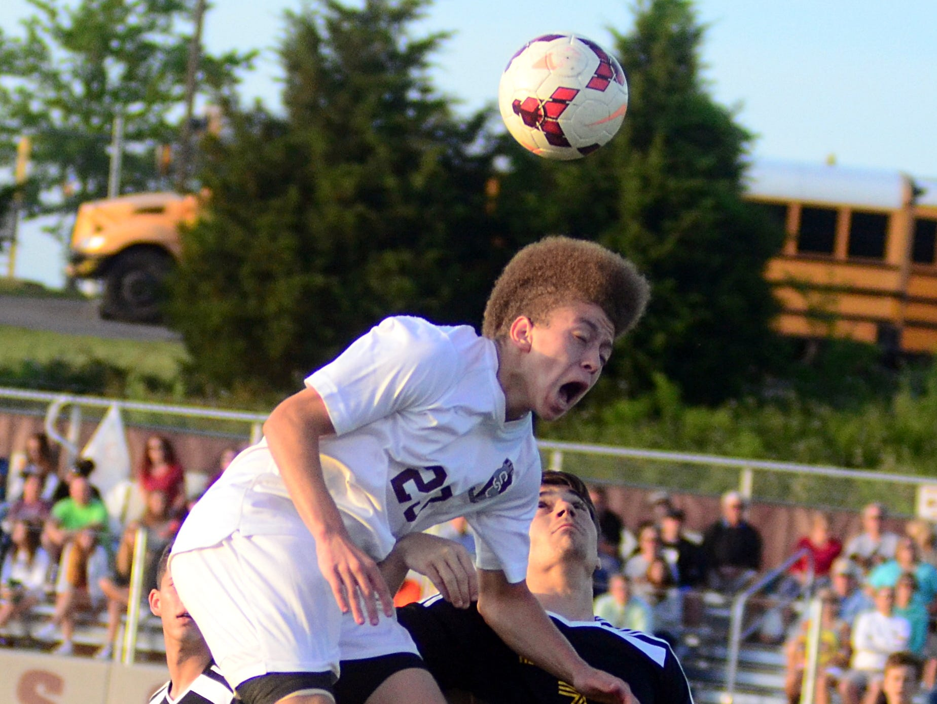 Station Camp High junior Chase Freeman elevates for a header against Hendersonville senior Thomas Roberts during first-half action. Freeman had a goal and an assist in the Bison's 2-1 victory on Thursday evening.