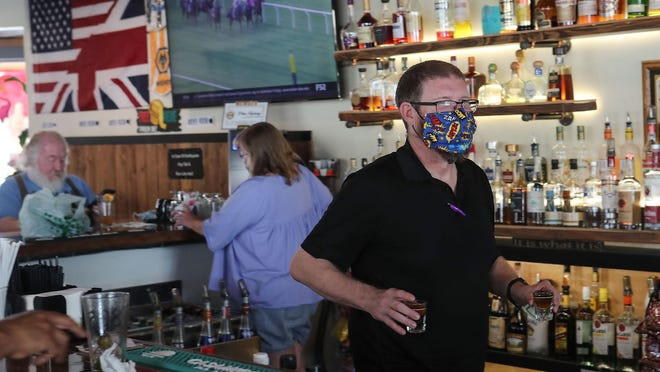 Josh Osborne tends bar at The Hair of the Dog in Palm Springs, Calif., June 12, 2020.