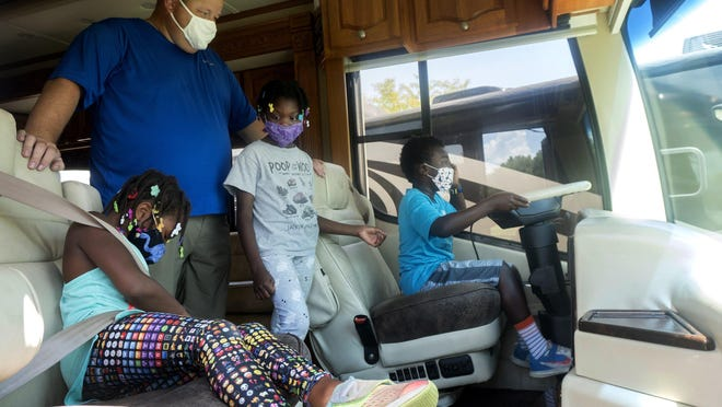 Kevin Zimmer examines the front of an RV with his children Georgia, left, 7, Laura, middle, 8, and Michael, right, 7, at Byerly RV Center in Eureka, Missouri on Saturday, August 22, 2020. The family originally bought an RV earlier this year to travel during the COVID-19 pandemic, but are now looking to upgrade to one with more space.