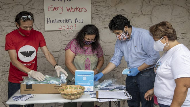 From left, Pedro Hernandez, Susana Almanza, David Chincanchan and Monica Allen are shown in May giving away away face masks at Tomgro Grocery in the Montopolis neighborhood.