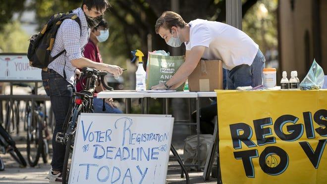 Deputy voter registrar Blake Zimmerman, right, helps professor Daniel Drucker register to vote at the University of Texas, ahead of the Nov. 3, 2020 elections. [AMERICAN-STATESMAN/FILE]