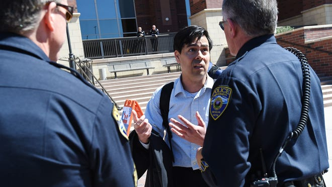 """Gun rights activist Adam Bridge is confronted by UNR police during a planned protest against the """"campus carry"""" bill at the University of Nevada in Reno on March 25, 2015."""
