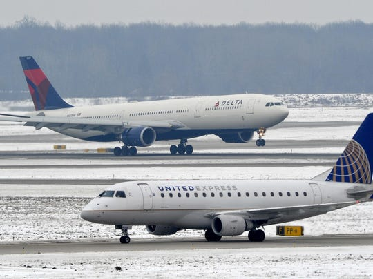 A United Express jet taxis as a Delta airliner touches down at Metro Airport.