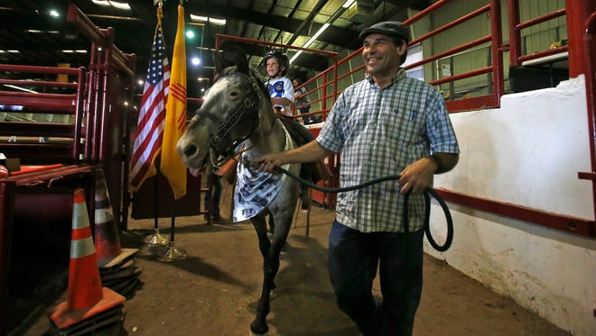 Braden Schrag rides Chiple with the help of his father Bob Schrag on Wednesday during a San Juan County Fair equestrian show for people with special needs in Memorial Coliseum at McGee Park in Farmington.