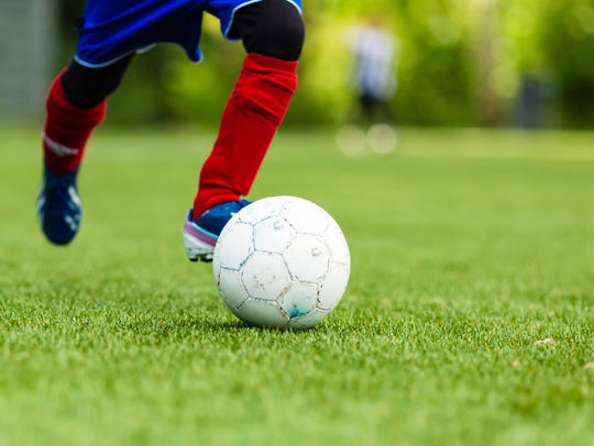 Picture of young soccer player dribbling with a soccer