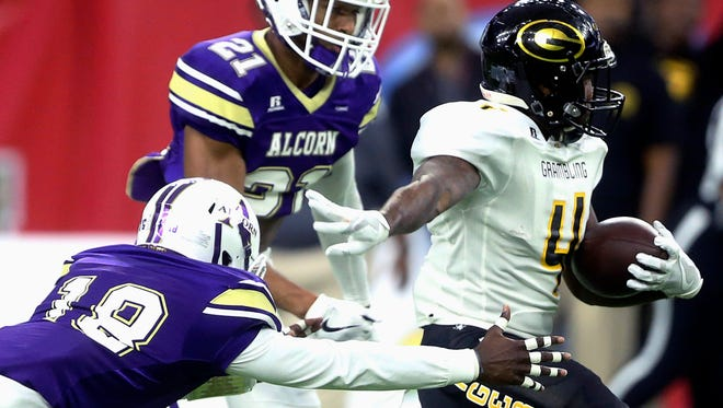 Grambling State's Martez Carter (4) is tackled by Alcorn State's Leishaun Ealey (18) and Jayron Harness (21) during the first quarter of the Southwestern Athletic Conference NCAA college football championship game Saturday, Dec. 3, 2016, in Houston. (Yi-Chin Lee/Houston Chronicle via AP)