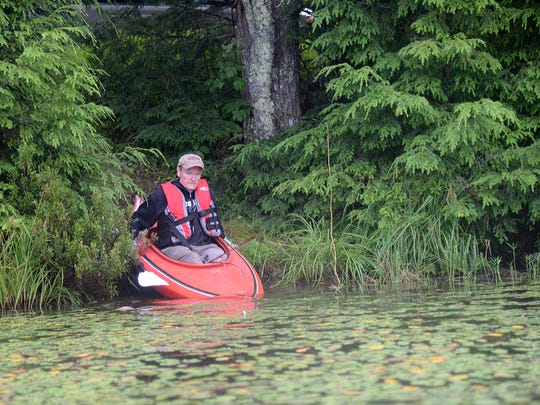 Larry Keen launches his kayak from an opening into a bass lake in Iron County.