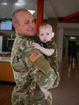 Mike Jacquard of Carroll holds his 4-month-old daughter, Ava Rae, during a sendoff for the 248th Aviation Support Battalion of the Iowa National Guard at Boone High School in Boone on Friday, Sept. 29, 2017.