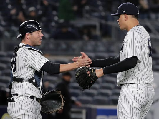 New York Yankees catcher Austin Romine (28) and pitcher Dellin Betances (68) shake hands after the Yankees beat the Miami Marlins 12-1 in a baseball game, Monday, April 16, 2018, in New York.