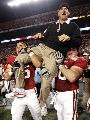 Then-Stanford coach Jim Harbaugh is lifted by players after Stanford's 40-12 victory over Virginia Tech in the Orange Bowl on Jan. 3, 2011.