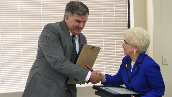 Gerald Cantrell (left), paramedic director for Baxter Regional Medical Center, receives a license from State Rep. Nelda Speaks on Friday. BRMC is the first in the state to receive community paramedic licenses.