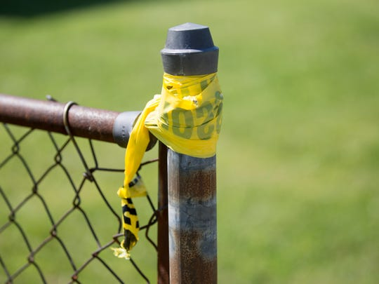 Crime scene tape is still tied to a fence at a Colerain