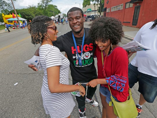 Devin Davis, center, president of WestCare Wisconsin Youth Action Council, hugs Tyla Sleight, left, and Annisa Nash, both of Milwaukee, during the 2017 Juneteenth Day celebration in Milwaukee.