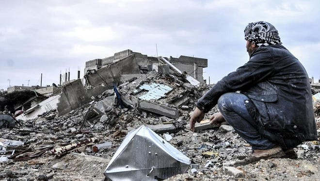 A man is seen near wreckage left by fighters in the center of the Syrian town of Kobani.