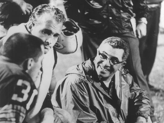 Vince Lombardi talks to Jim Taylor (31) and Paul Hornung