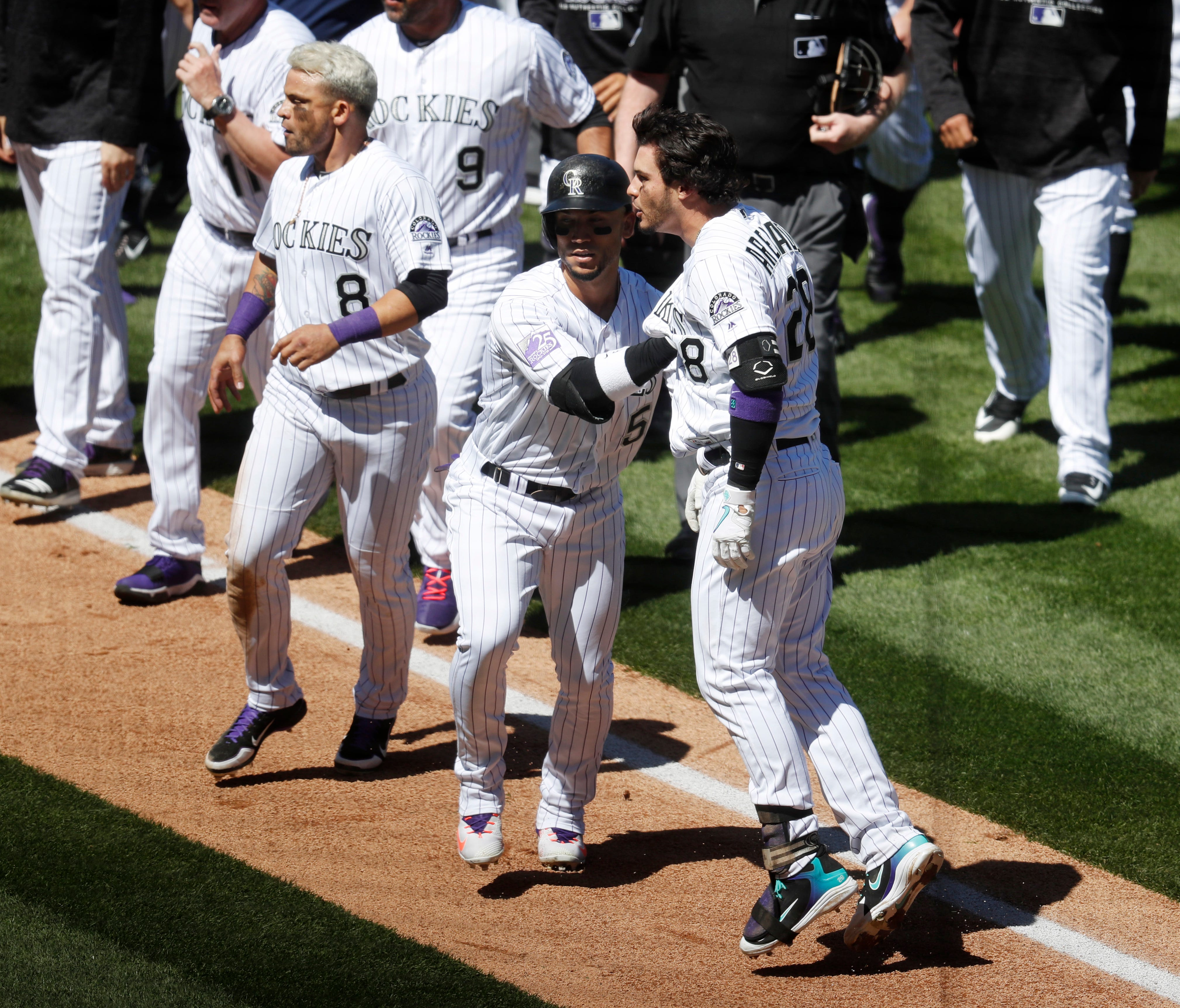 Rockies' Nolan Arenado, front right, is restrained by Carlos Gonzalez.