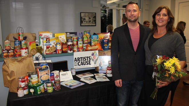 Artists for a Cause Founder Terry Barber stands with Dance for Food Director Anna Preston in front of food donated at a Dance for Food event.