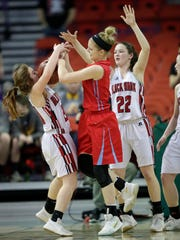 Newman Catholic's Signe Fronek, center, battles for