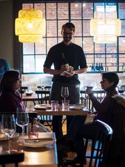 Diners sample a wine at the wine bar at the new Dedalus