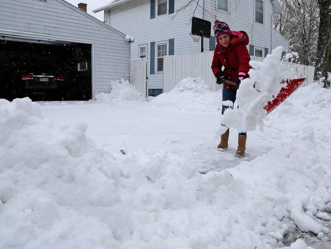 Claudia Martinez of Sheboygan shovels snow out of her
