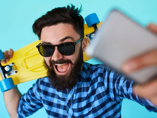 Young hipster with beard in glasses taking selfie and smiling