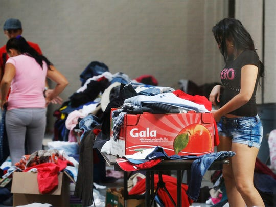 A Cuban immigrant at Houchen Community Center on Wednesday afternoon looks through piles of clothes donated for those who arrive at the center with little or no clothing.