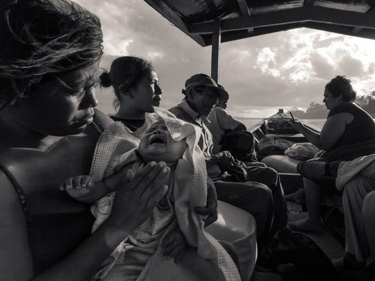 A mother takes her child on a boat for medical attention. University of Delaware faculty member Jon Cox collaborated with Andrew Bale of Dickinson College on the photographic portion of a cultural study of the Ese'Eja people in Peru, a threatened culture in the Amazon rainforest.