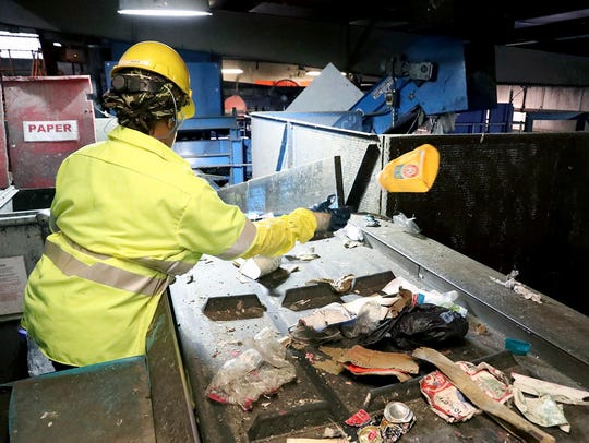 Workers at ACUA recycling center pull plastic contaminants