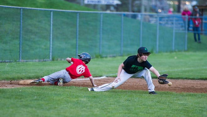 Ben Briggs, 12, tries to field a ball as an opposing player slides safely into third base during their Staunton Kiwanis baseball game at Gypsy Hill Park on Monday, April 27, 2015.