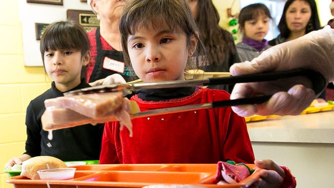 Yahaira Rosales, 6, right,  blankly stares while her tray is filled with large slices of ham on Friday during the annual Christmas dinner on Friday, December 25, 2015, at El Caldito Soup Kitchen. On the menu was ham with pineapple, a corn and bean medley, stuffing, gravy, salad and bread.