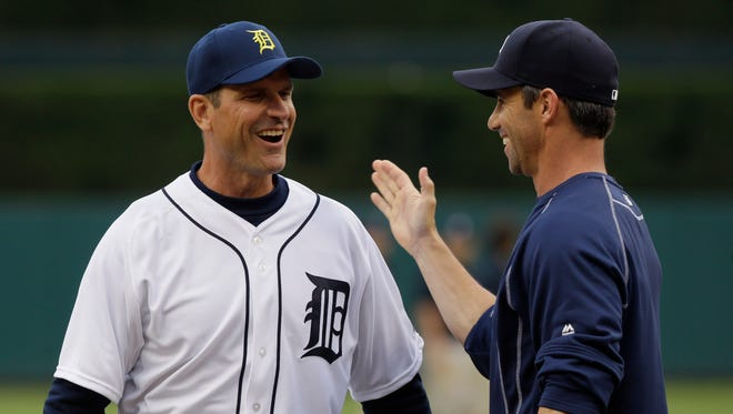Michigan football coach Jim Harbaugh shakes hands with Detroit Tigers manager Brad Ausmus after throwing the first pitch before the first inning of a baseball game between the Detroit Tigers and the Pittsburgh Pirates, Tuesday, June 30, 2015, in Detroit.