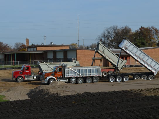 Construction crews dumping dirt outside Lansing's Fairview