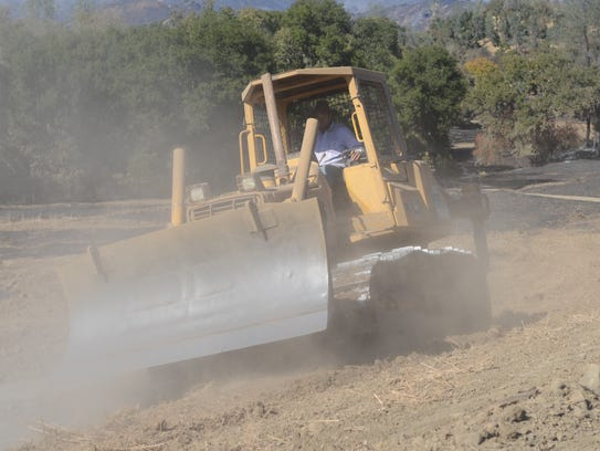 A resident of Capell Valley, Calif., runs a bulldozer