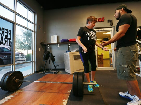 Paula Powell discussed grip positioning for lifting the weight bar Friday with trainer Jonathan Ramos.