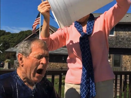 "Former First Lady Laura Bush pours icy water on her husband, President George W. Bush as part of the ""Ice Water Challenge."""