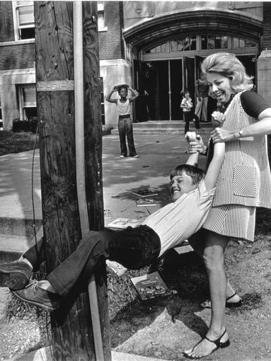 """Third grader Kevin Huber gave the impression that he wasn't yet ready for summer vacation to end, as shown in this photo published on the first day of classes at School 54 on Sept. 4, 1973. The bit of horseplay was all in fun as teacher Carole Hon """"coaxed"""" Huber off a light pole in front of the school at 10th and Dearborn Streets."""
