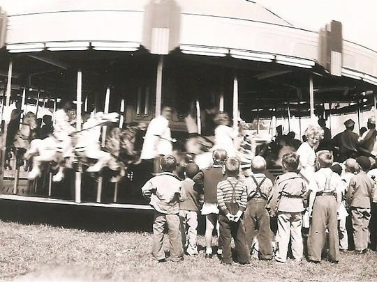A carousel attracts a crowd of children during Fred Lake's second-generation ownership of a family carnival business in Wisconsin.