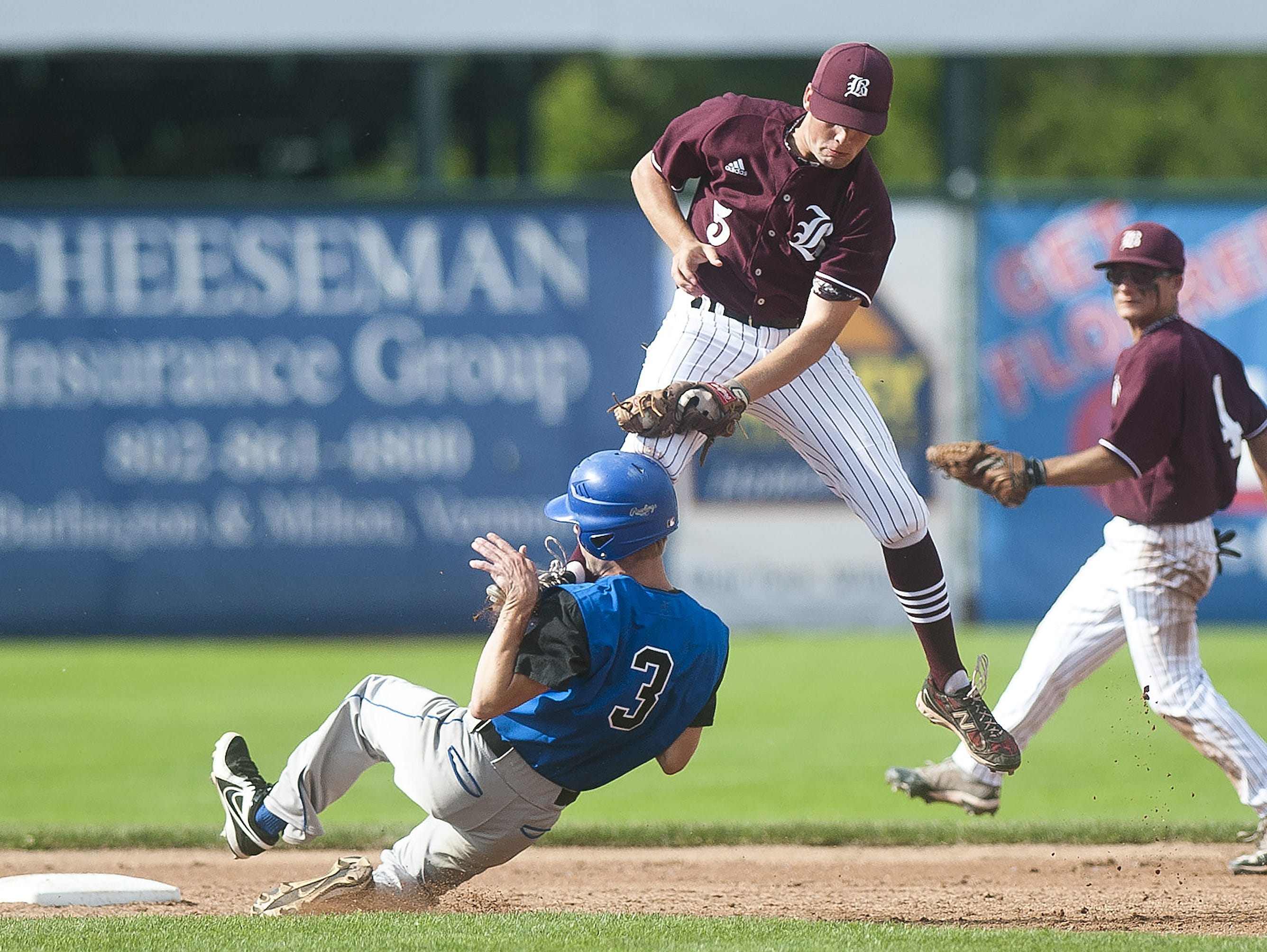 Williamstown's Curtis Gauthier, left, slides into second base under the tag by BFA-Fairfax shortstop Jared Quick during the Division III state championship game on Saturday at Centennial Field.