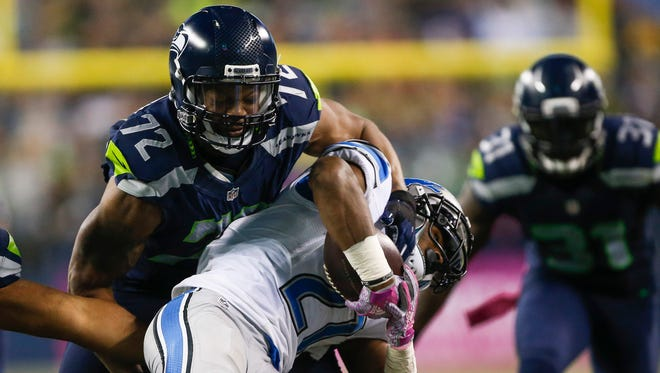 Seattle Seahawks defensive end Michael Bennett (72) tackles Detroit Lions running back Ameer Abdullah (21) during the third quarter  at CenturyLink Field.