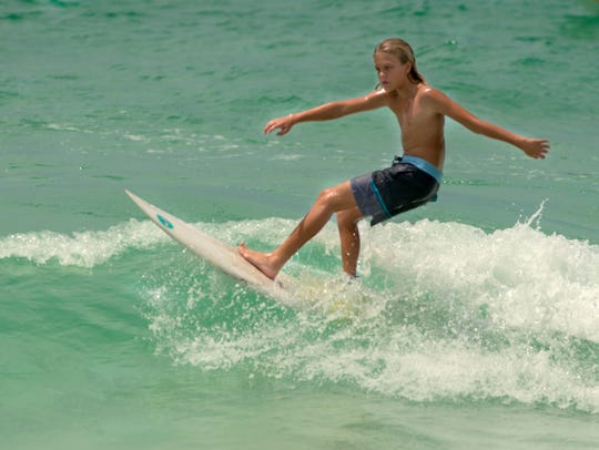 Surfer Noah Allen takes to the waves Saturday, May