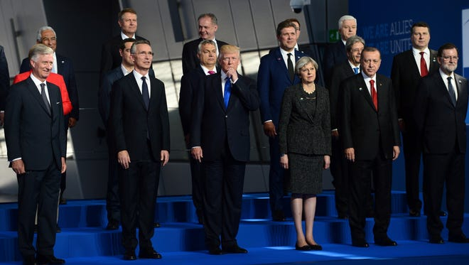 President Trump, center, flanked by British Prime Minister Theresa May, third from right, and NATO Secretary General Jens Stoltenberg, second from left, joins fellow leaders in a group photo at NATO headquarters during the NATO Summit in Brussels, Belgium on May 25, 2017.