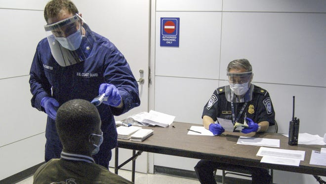 A member of the U.S. Coast Guard (upper left) takes the temperature of an arriving passenger as a Customs and Border Protection officer examines documents during screening for the Ebola virus at O'Hare International Airport in Chicago, Ill., on Oct. 16, 2014.