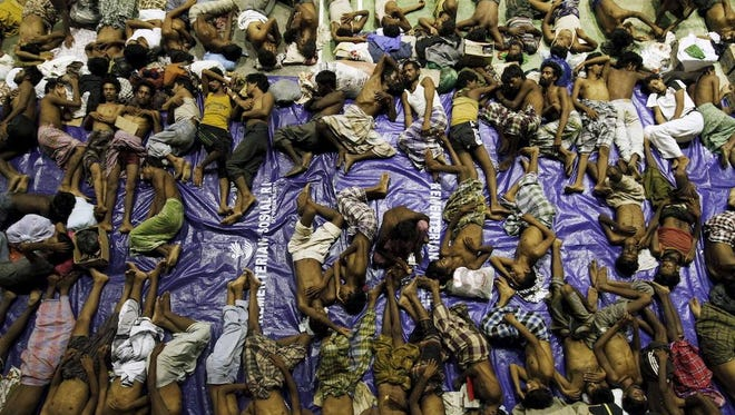 Migrants believed to be Rohingya rest inside a shelter after being rescued from boats in Indonesia's Aceh province on May 11.