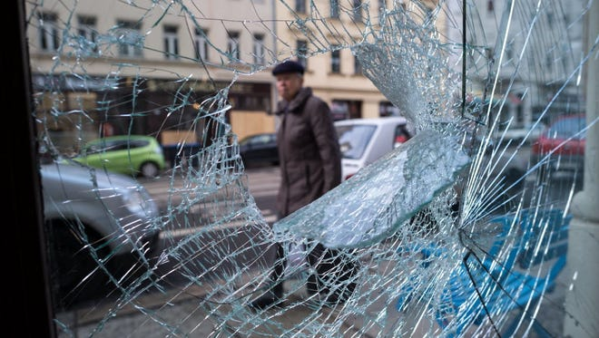 A man walks past the shattered windows of a launderette in Leipzig, Germany, on Jan. 12, 2016, the day after right-wing supporters rioted in the city.