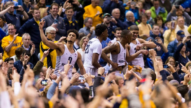 Marquette players celebrate with fans after the Golden Eagles' win over Villanova.