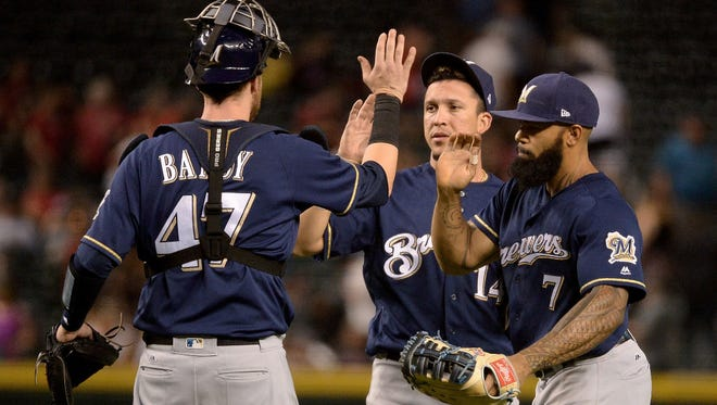 Jett Bandy (from left), Hernan Perez and Eric Thames celebrate after the Brewers beat the Diamondbacks on Friday night.