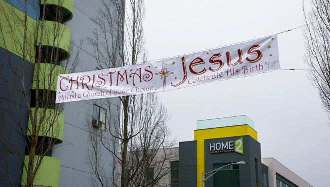In this Friday, Dec. 15, 2017 photo, a banner stretches across West 11 St. in Eugene, Ore. encouraging church attendance for Christmas. An atheist is demanding that city officials remove the banner that he believes is a violation of church and state.