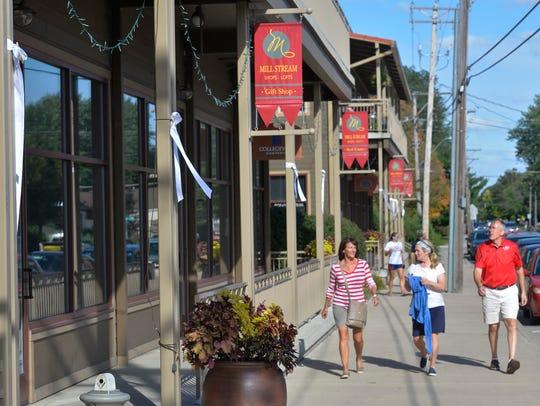 Pedestrians walk past white ribbons hung along Minnesota