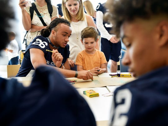 Mason Barry, 4 of Lebanon County, colors with Penn State football player Jonathan Sutherland at Penn State Children's Hospital Thursday, July 13, 2017, in Hershey.
