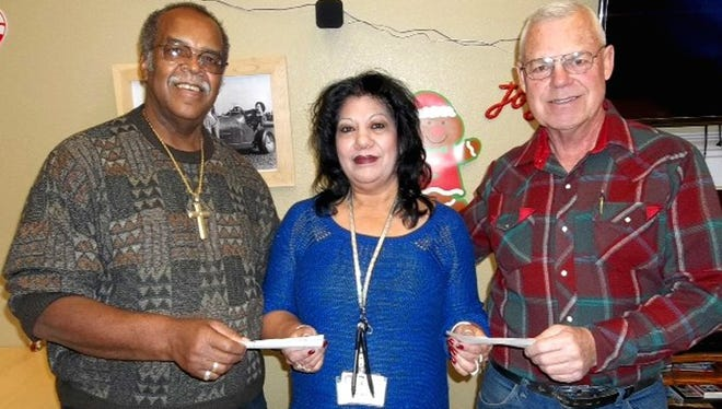 Mary Muniz, an activity profession at Fort Bayard Medical Center, receives donations from David Fischer, secretary of Santa Rita Lodge, at right, and from the Rev. Earseye Ross, secretary of Silver City Lodge, at left.